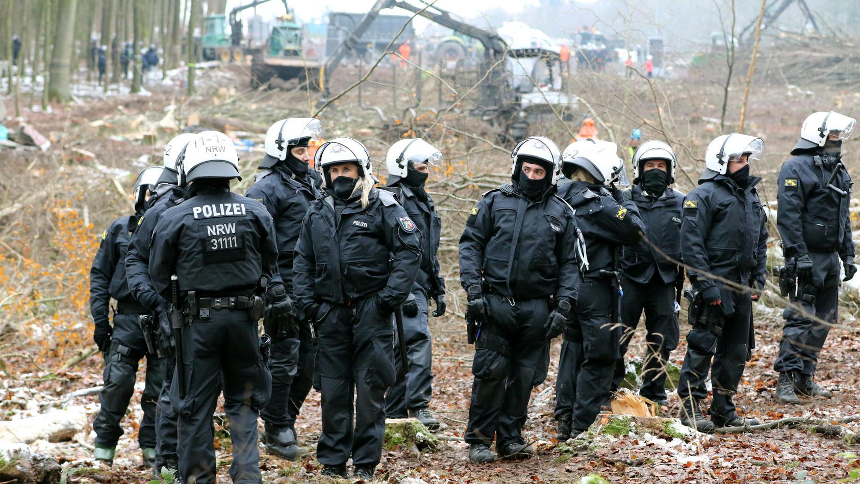 Polizisten stehen am 03.12.2020 vor einem sogenannten Harvester, der für die A49-Trasse Bäume rodet.