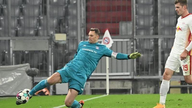 Münchens Torwart Manuel Neuer (l) und Leipzigs Alexander Sörloth kämpfen um den Ball. Foto: Sven Hoppe/dpa