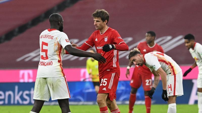 Leipzigs Dayot Upamecano (l) und Münchens Thomas Müller umarmen sich nach dem Spiel. Foto: Sven Hoppe/dpa