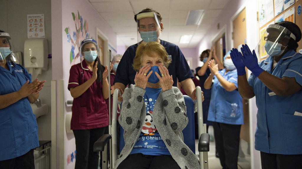 Margaret Keenan, 90, is applauded by staff as she returns to her ward after becoming the first patient in the UK to receive the Pfizer-BioNTech COVID-19 vaccine, at University Hospital, Coventry, England, Tuesday Dec. 8, 2020. The United Kingdom, one