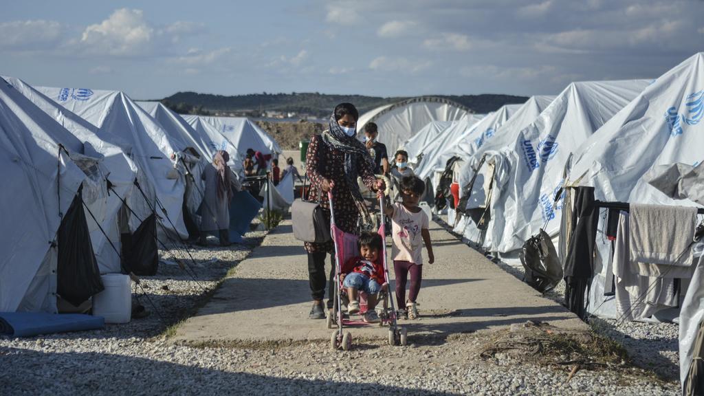 """ARCHIV - 14.10.2020, Griechenland, Lesbos: Migranten gehen nach einem starken Regenfällen durch das Flüchtlingslager «Kara Tepe». (zu dpa """"Spiegel:Deutschland soll bis zu 5000 Flüchtlinge mehr aufnehmen"""") Foto: Panagiotis Balaskas/AP/dpa +++ dpa-Bil"""