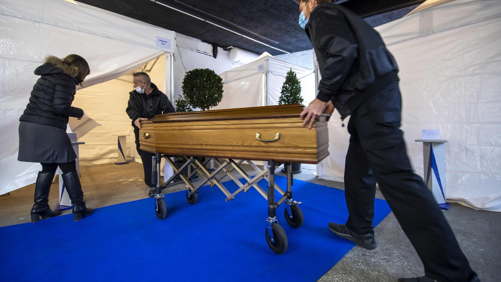 Bestattungshelfer bringen einen Sarg in ein Zelt, das als provisorische Grabkammer dienen soll. Das Zelt wird in einem Lagerhaus installiert, damit sich Angehörige sicher zu einer Abschiedsfeier versammeln können.