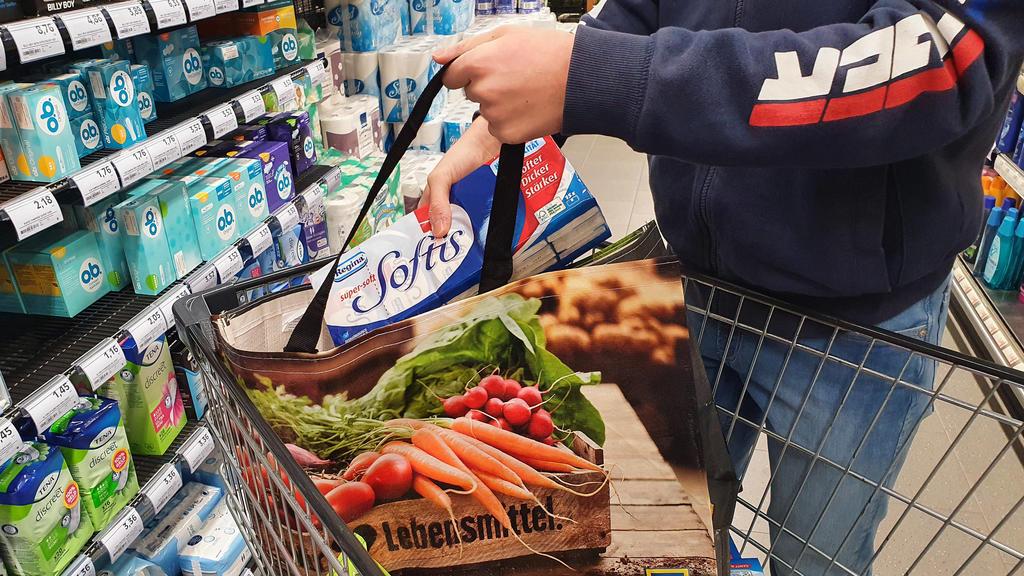 In einer Aldi-Filiale sieht man einen Mann einkaufen. In seinem Einkaufswagen liegen seine Einkäufe, unter anderem unverpacktes Gemüse.