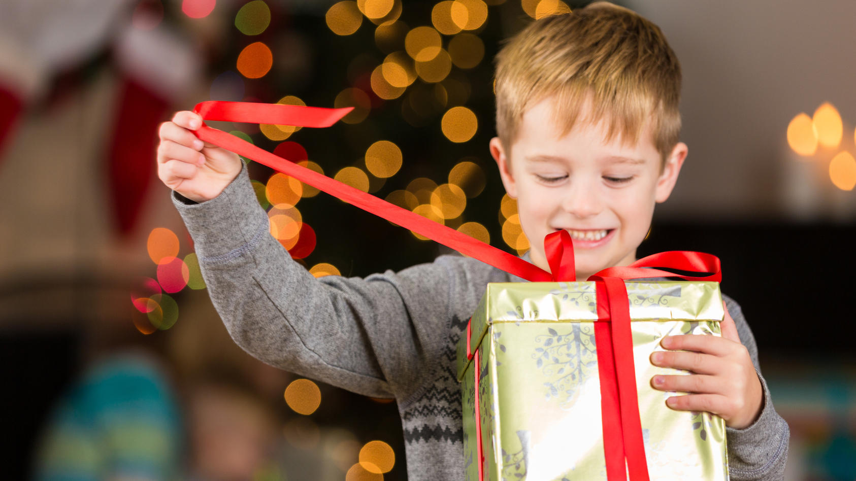 Junge öffnet Weihnachtsgeschenk