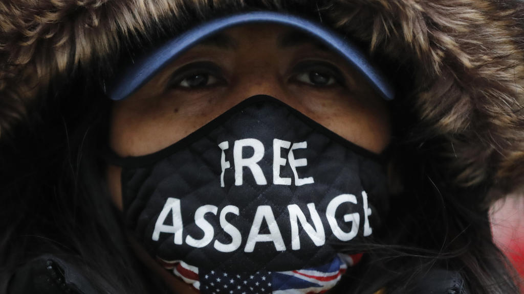 A Julian Assange supporter wears a face mask bearing his name outside the Old Bailey in London, Monday, Jan. 4, 2021. Judgement is to be made by Judge Vanessa Baraitser on Julian Assange's his extradition hearing to the US. Assange has been charged u