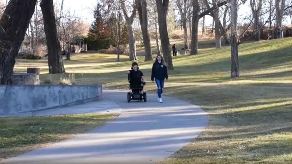Mann in Rollstuhl und Frau auf Weg