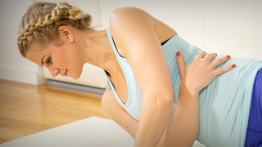 Junge Frau in Sportkleidung macht eine Pilates-Übung