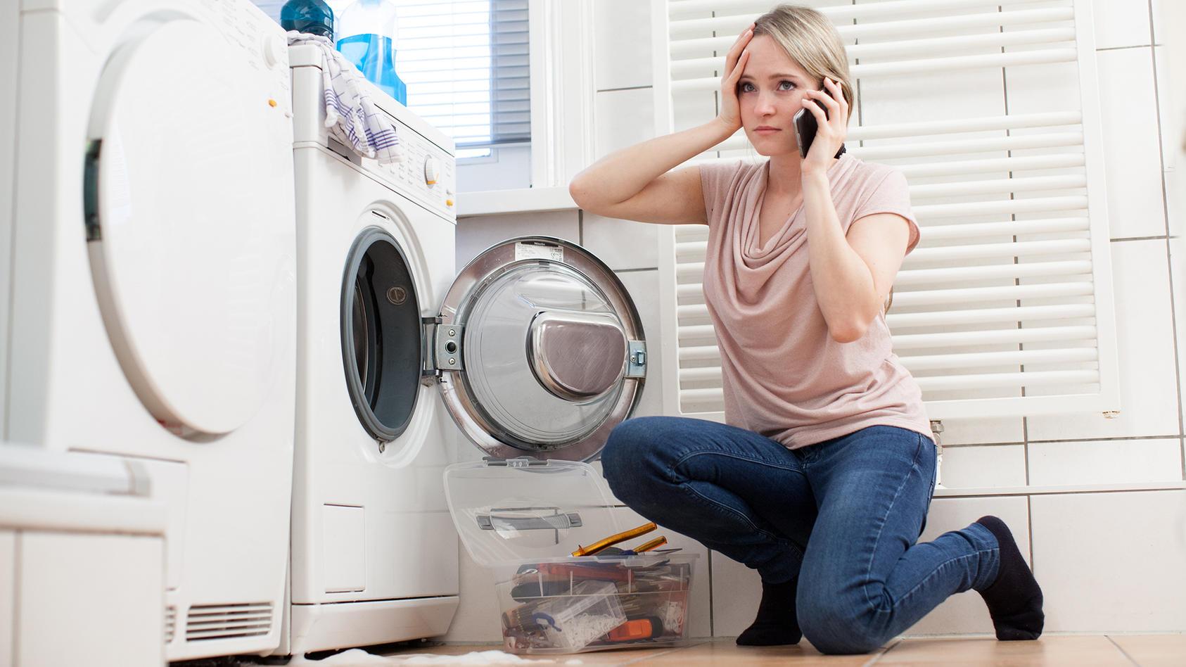 Eine junge Frau telefoniert mit einem Handwerker, nachdem ihre Waschmaschine Leck geschlagen ist.