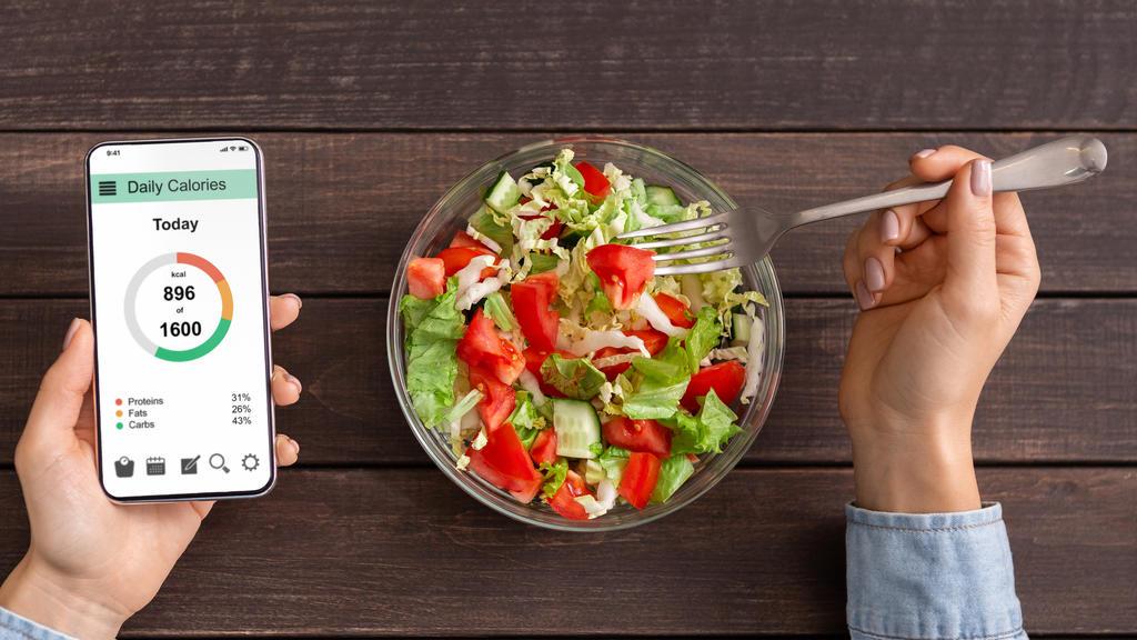 Frau isst Salat und zählt die Kalorien