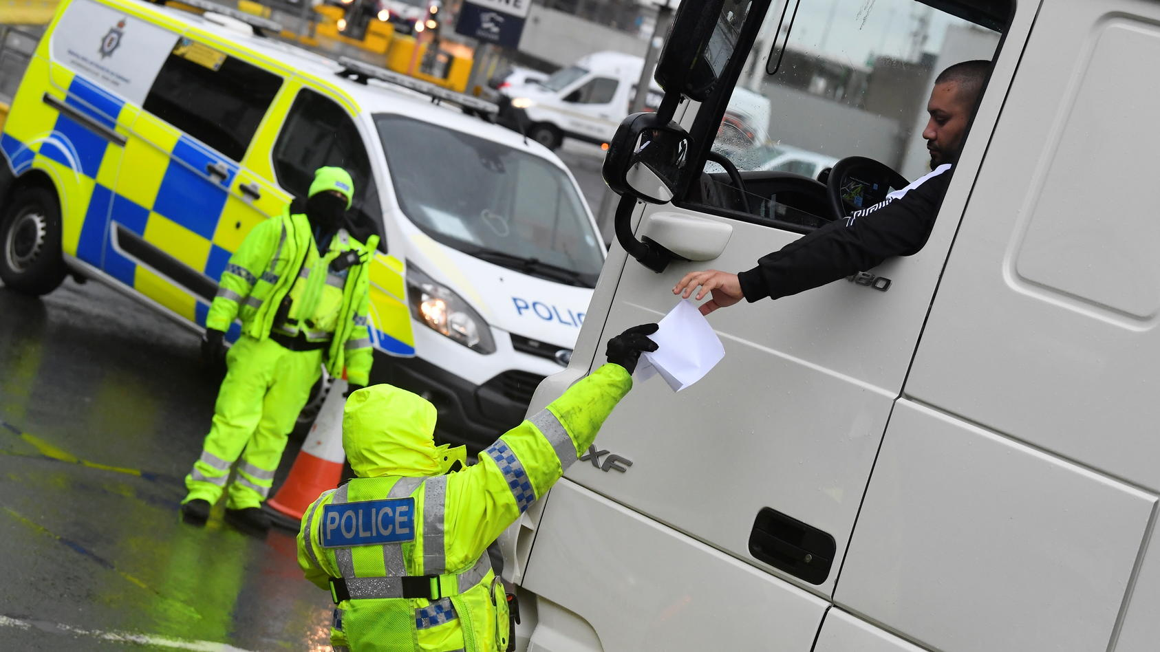 A police officer checks the documentation of a lorry driver upon his arrival to the Port of Dover