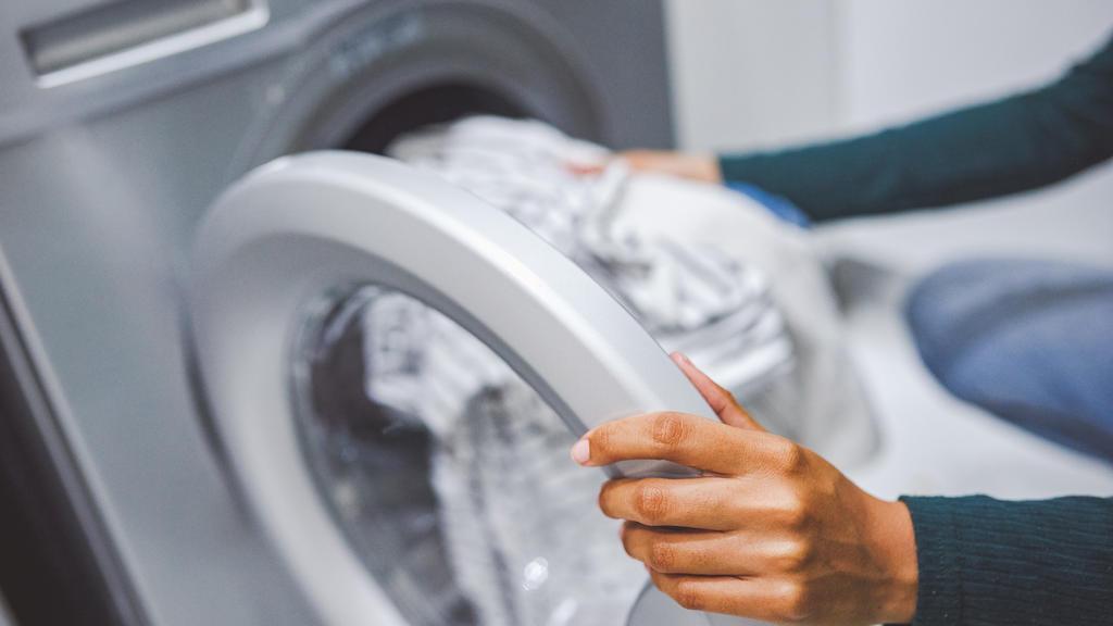 Frau legt Wäsche in Waschmaschine