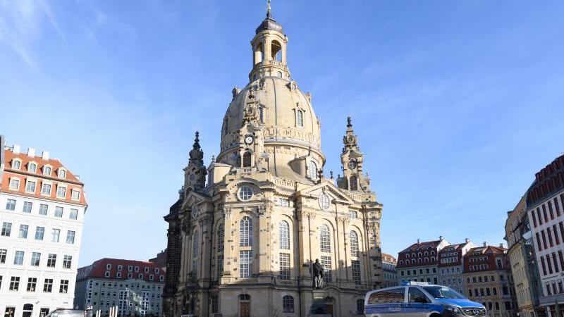Ein Polizeiauto steht vor der Frauenkirche auf dem Neumarkt. Foto: Sebastian Kahnert/dpa-Zentralbild/dpa