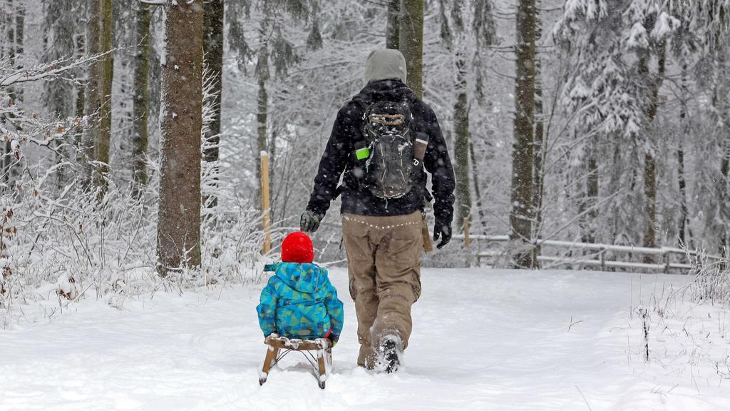 Ein Vater zieht sein Kind auf einem Schlitten, während er durch den Schnee stiefelt.