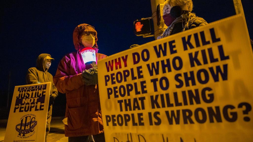 12.01.2021, USA, Bloomington: Glenda Breeden (M) aus Bloomington, Aktivistin gegen die Todesstrafe, hält eine Lampe, bei einem Protest gegen die Hinrichtung von Lisa Montgomery und zwei weiteren Personen im Gefängnis in Terre Haute im US-Bundesstaat