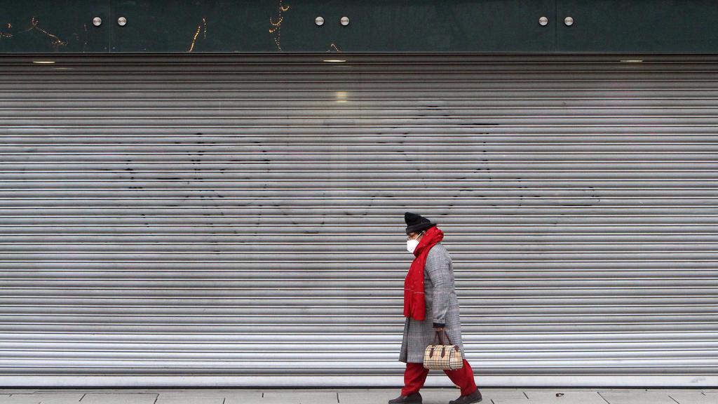 Eine Frau mit Maske geht an einer mit Rolltor verschlossenen Filiale der Modekette Primark in der Einkaufsstraße und Fußgängerzone Zeil in der Innenstadt von Frankfurt vorbei, Hessen, Deutschland *** A woman wearing a mask walks past a store of the