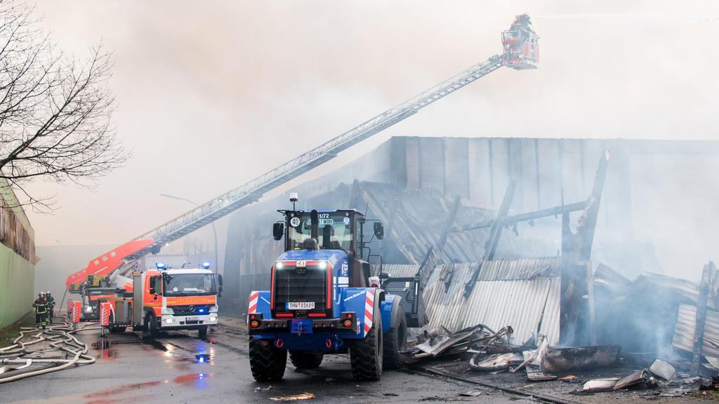 13.01.2021, Hamburg: Feuerwehrleute löschen im Stadtteil Wilhelmsburg einen Großbrand mit Hilfe eines Radladers des THW. Eine Lagerhalle in einem Gewerbegebiet steht seit dem Morgen im Vollbrand. Foto: Daniel Bockwoldt/dpa +++ dpa-Bildfunk +++