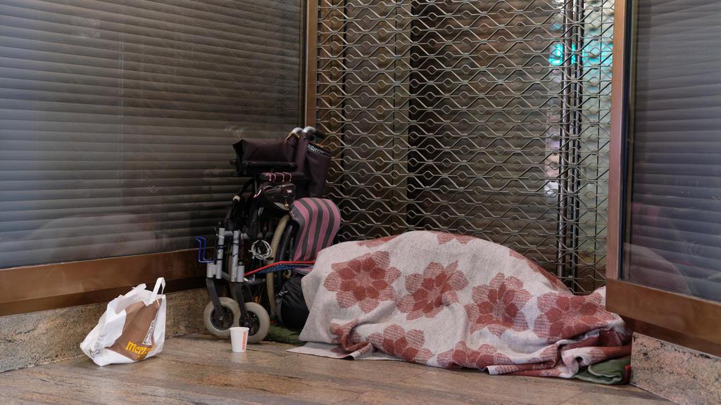 11.01.2021, Nordrhein-Westfalen, Köln: Ein Mensch liegt in der Innenstadt in einem Schlafsack im Eingang zu einem Geschäft. Besonders für Wohnungslose ist der Lockdown eine harte Zeit. Durch die fehlenden Touristen und Einkaufenden fehlen auch die Ei