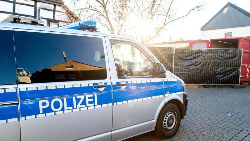 Ein Einsatzfahrzeug der Polizei fährt vor einem Haus entlang, das von Polizeikräften durchsucht wird. Foto: Hauke-Christian Dittrich/dpa/Symbolbild