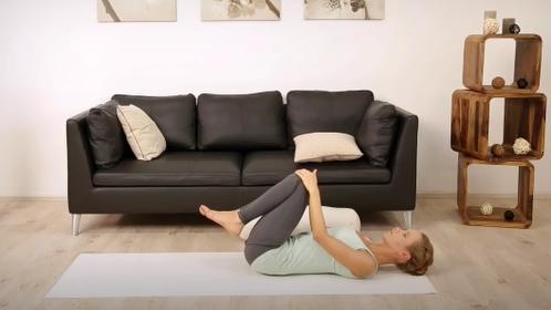 Yoga-Trainerin liegt mit angewinkelten Beinen auf dem Rücken