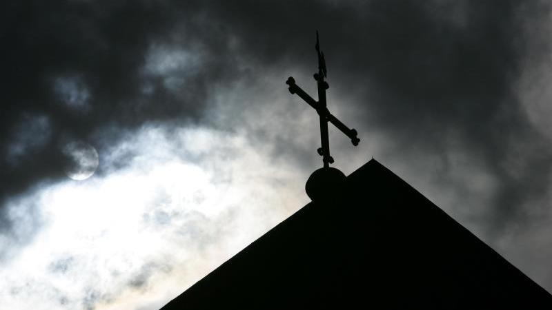 Ein Kreuz steht vor wolkenverhangenem Himmel auf dem Dach einer Kirche. Foto: Friso Gentsch/dpa/Symbolbild