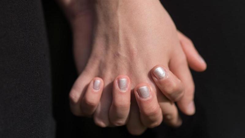 Zwei lesbische Frauen fassen sich an den Händen (gestellte Szene). Foto: picture alliance / dpa/Symbolbild