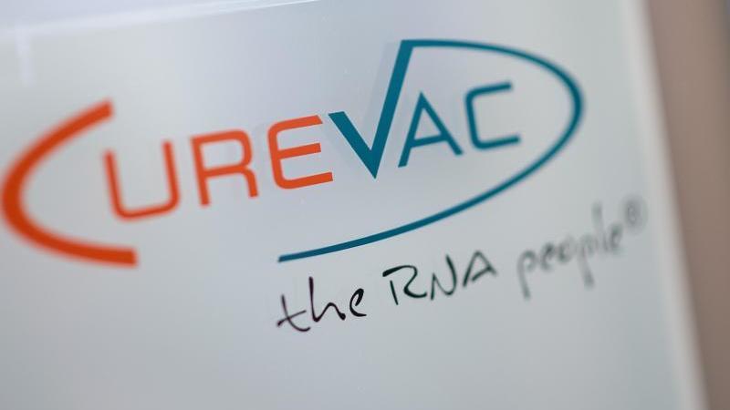 """Das Logo des biopharmazeutischen Unternehmens CureVac steht mit dem Slogan """"the RNA people"""" auf einer Scheibe. Foto: Sebastian Gollnow/dpa/Archivbild"""