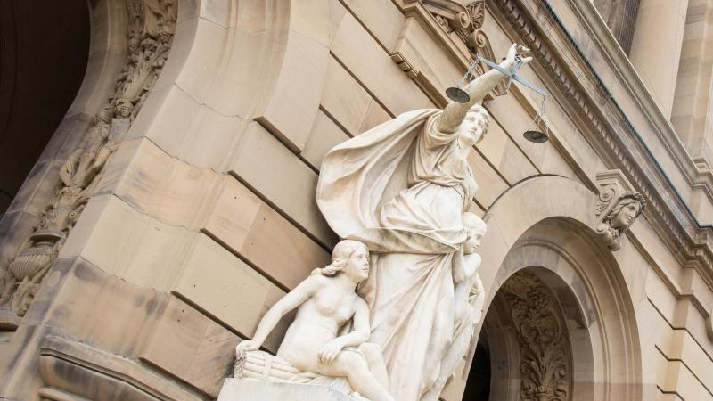 Vor einem Gerichtsgebäude hält eine Statue der Justitia eine Waagschale. Foto: Stefan Puchner/dpa/Archivbild