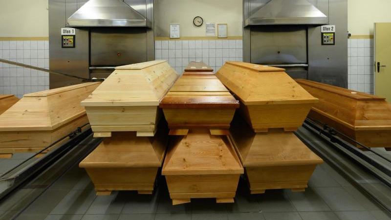 Särge mit Verstorbenen stehen in einem Krematorium vor dem Einäscherungsofen. Foto: Robert Michael/dpa-Zentralbild/dpa/Archivbild