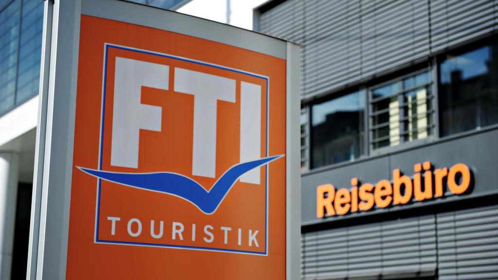 ARCHIV - 03.03.2014, Bayern, München: Das Logo des Reiseveranstalters FTI-Touristik steht vor einem Reisebüro. Europas drittgrößer Reiseveranstalter FTI steckt durch die Corona-Krise in Geldnot, bekommt jetzt Staatshilfe und gibt einen großen Teil se