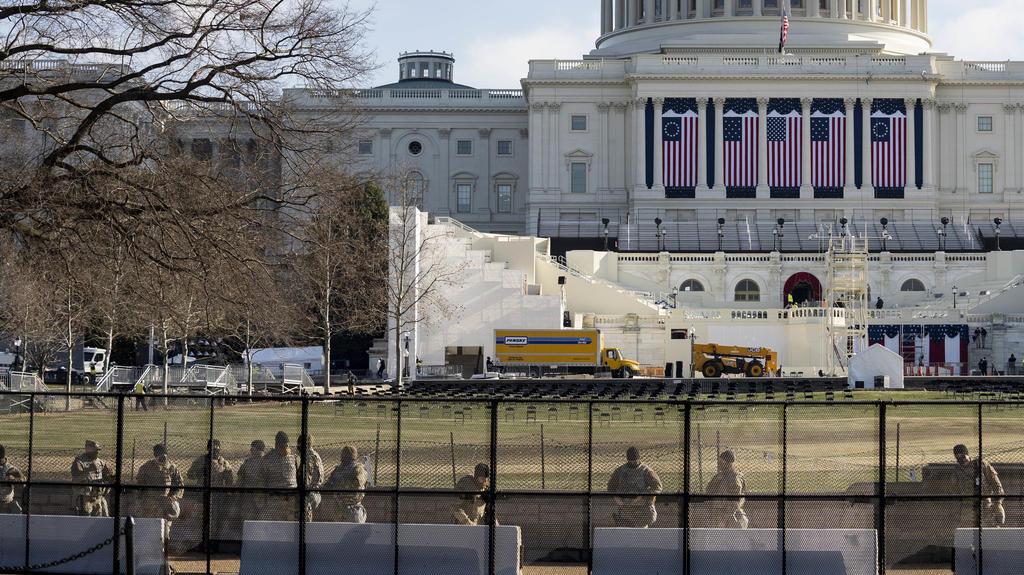13.01.2021, USA, Washington: Mitglieder der Nationalgarde sichern das Gebiet um das US-Kapitol, vor dem die Aufbauarbeiten für die Zeremonie zur Amtseinführung des gewählten US-Präsidenten Biden stattfinden. Das Repräsentantenhaus hat mit der Beratun