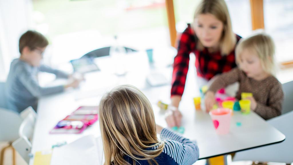 dpatopbilder - 14.01.2021, Nordrhein-Westfalen, Haltern am See: Eine Lehrerin sitzt mit ihren drei Kindern im Wohnzimmer, unterrichtet ihre Schüler einer Berufsschule im Distanzunterricht und hilft ihren Kindern bei ihren Aufgaben für die Schule. Um