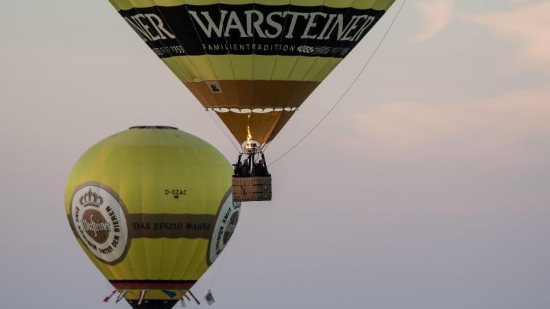 Zwei Warsteiner Heißluftballon fahren im Abendlicht. Foto: Bernd Thissen/dpa/Symbolbild