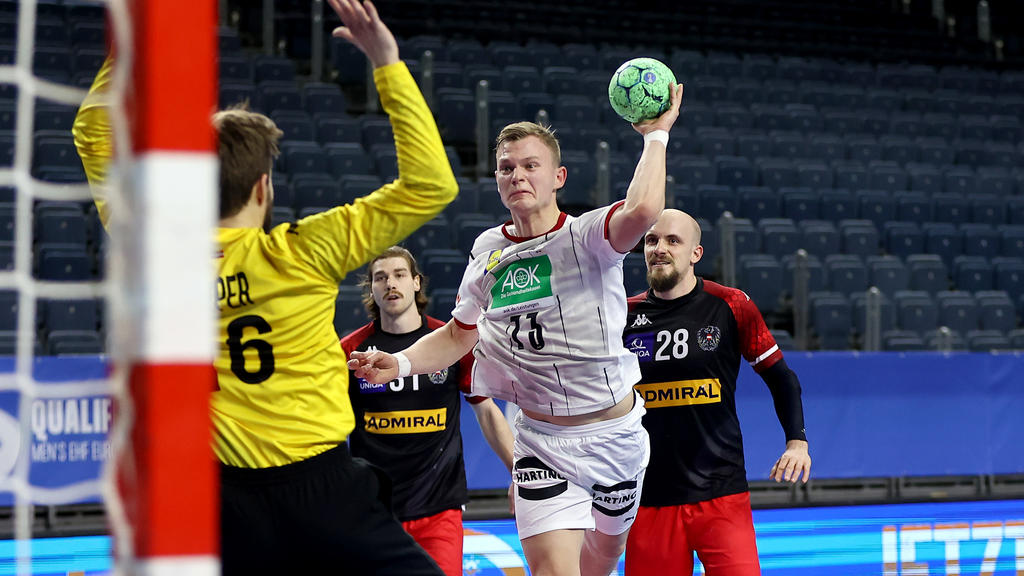 COLOGNE, GERMANY - JANUARY 10: Timo Kastening of Germany (R) scores a goal against Florian Kaiper of Austria (L) during the Handball EURO Qualification match between Germany and Austria at Lanxess Arena on January 10, 2021 in Cologne, Germany. (Photo