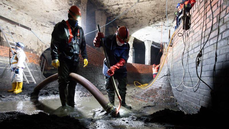 Kanalarbeiter reingen das Sielzusammenführungsbauwerk im Pumpwerk Hafenstraße. Foto: Christian Charisius/dpa/Archivbild