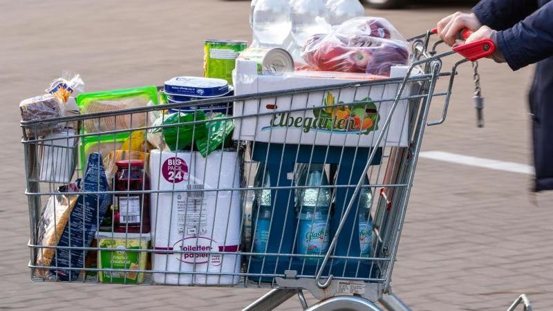 Ein Einkaufswagen mit Lebensmitteln und Produkten des täglichen Bedarfs wird über den Parkplatz eines Supermarkts geschoben. Foto: Jens Büttner/dpa/Archivbild