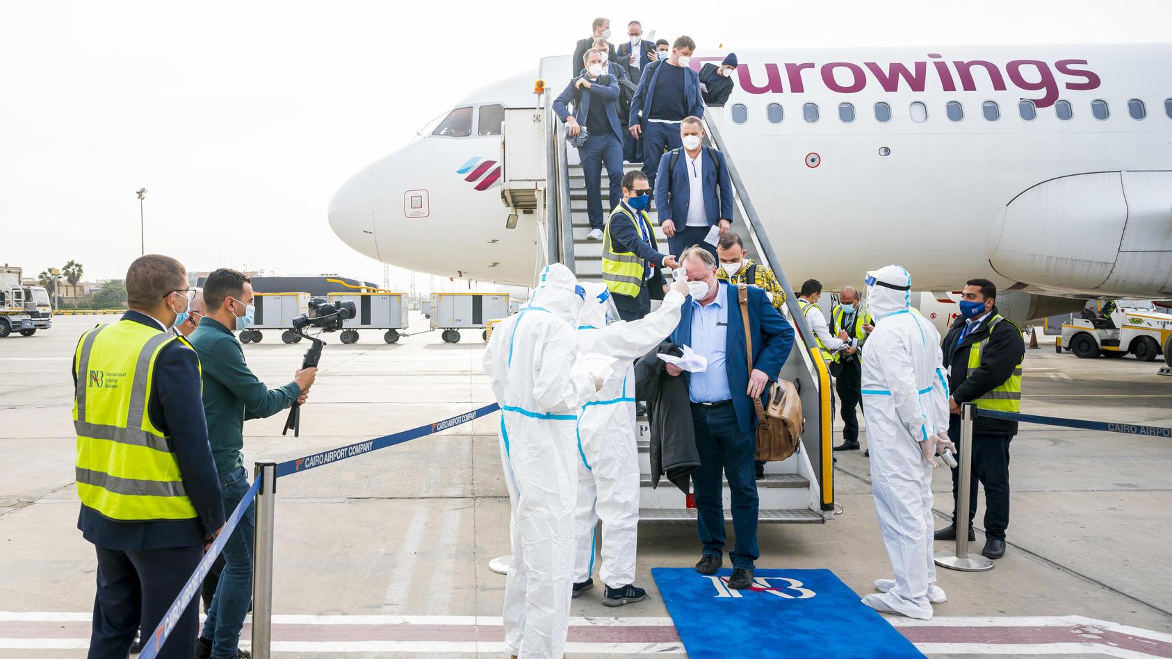Medizinisches Personal empfängt Teilnehmer der Handball-WM am Flughafen.