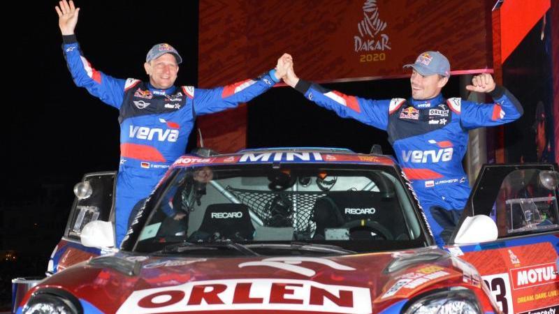 Navigator Timo Gottschalk (l) und Fahrer Jakub Przygonski vom Team Orlen X-Raid feiern auf dem Podium. Foto: -/Saudi Press Agency/dpa/Archivbild