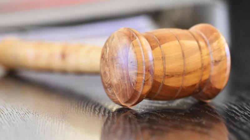 Ein Richterhammer aus Holz liegt auf der Richterbank. Foto: Uli Deck/dpa