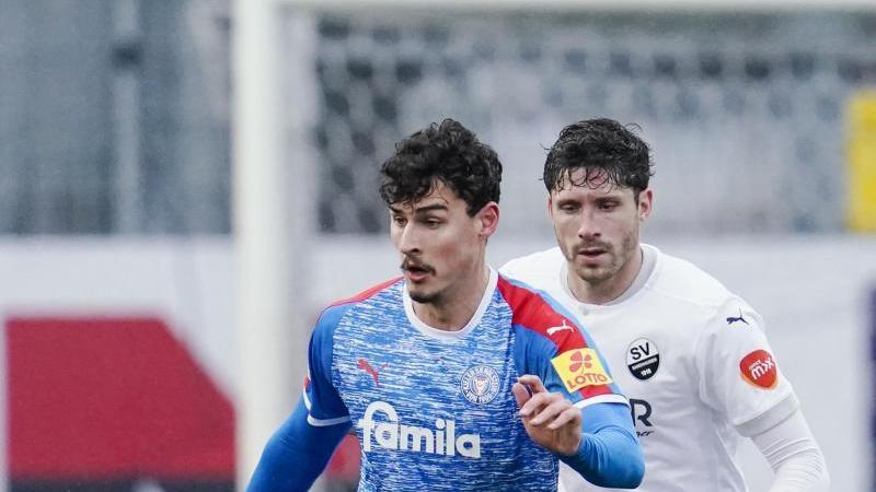 Kiels Janni-Luca Serra (vorne) und Sandhausens Tim Kister kämpfen um den Ball. Foto: Uwe Anspach/dpa