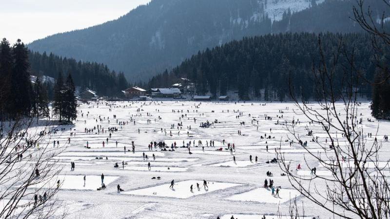 Zahlreiche Ausflügler tummeln sich am 9.1.2021 auf dem zugefrorenen Spitzingsee. Foto: Matthias Balk/dpa/Archivbild