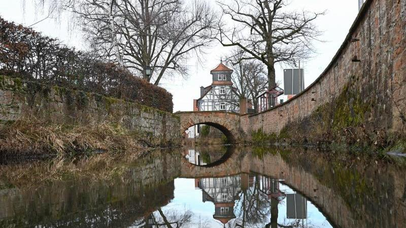Ein Fachwerkhaus und eine alte Steinbrücke spiegeln sich in Bleichenbach im gleichnamigen Bach. Foto: Arne Dedert/dpa/Archivbild