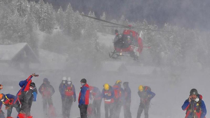 Ein Helikopter landet hinter Helfern der Bergrettung. Foto: Thomas Sehr/dpa