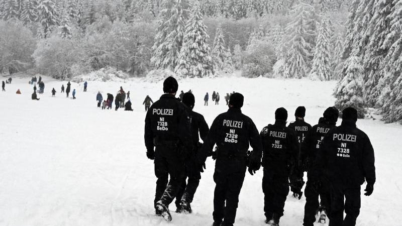 """Polizisten gehen über die Rodelpiste """"Brockenblick"""" im Harz. Foto: Swen Pförtner/dpa/Symbolbild"""