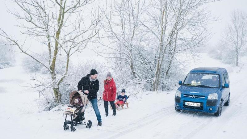 Eine Familie geht an einer verschneiten Straße spazieren. Foto: Ole Spata/dpa/Symbolbild