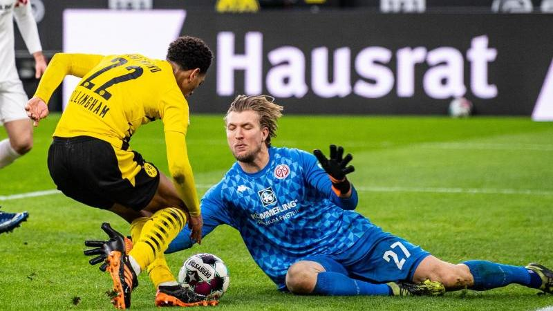 Der Mainzer Torwart Robin Zentner (r) sptitzelt Dortmunds Jude Bellingham den Ball vom Fuß. Foto: Guido Kirchner/dpa-Pool/dpa