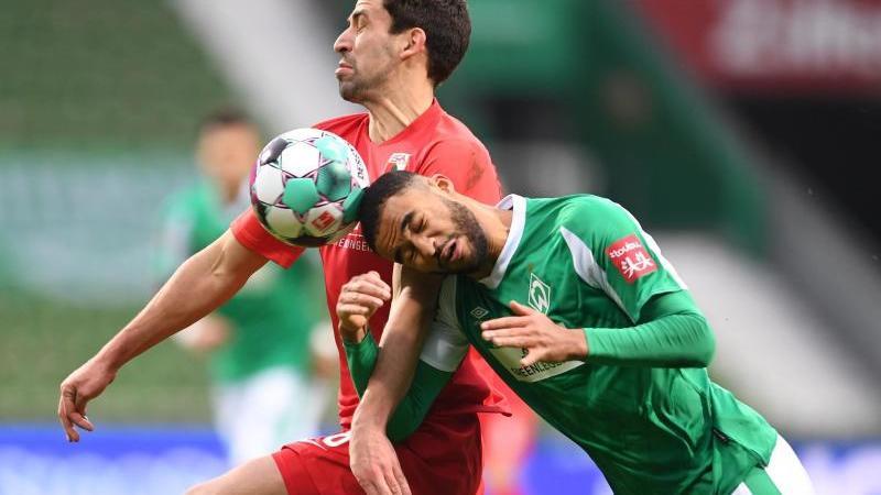 Bremens Jean-Manuel Mbom (r) versucht sich gegen Augsburgs Rani Khedira durchzusetzen und den Ball mit dem Kopf zu spielen. Foto: Carmen Jaspersen/dpa