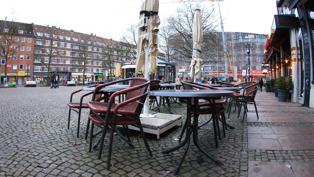 Aufeinander gestapelte Stühle stehen vor einem geschlossenen Restaurant auf dem menschenleeren Winterhuder Marktplatz in Hamburg. Winterhude Hamburg *** Chairs stacked on top of each other stand in front of a closed restaurant on the deserted Winter