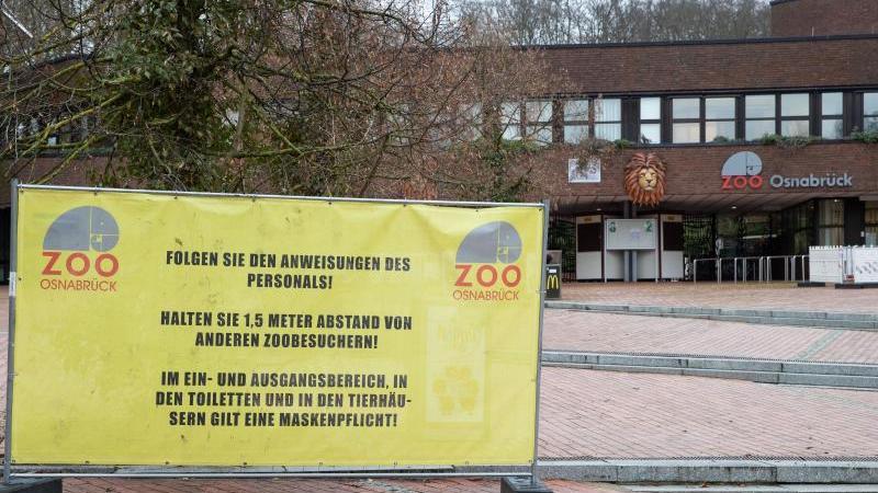 Auf Abstand zu anderen Zoobesuchern wird auf einem Plakat gebeten. Foto: Friso Gentsch/dpa/Symbolbild