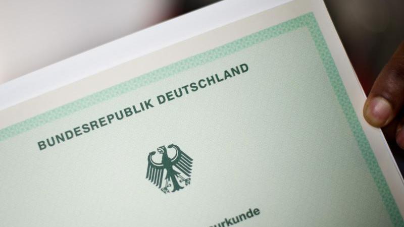 Ein Mann hält bei einer Einbürgerungszeremonie eine Einbürgerungsurkunde der Bundesrepublik Deutschland im Neuen Rathaus in Hannover in der Hand. Foto: Julian Stratenschulte/dpa/Symbolbild