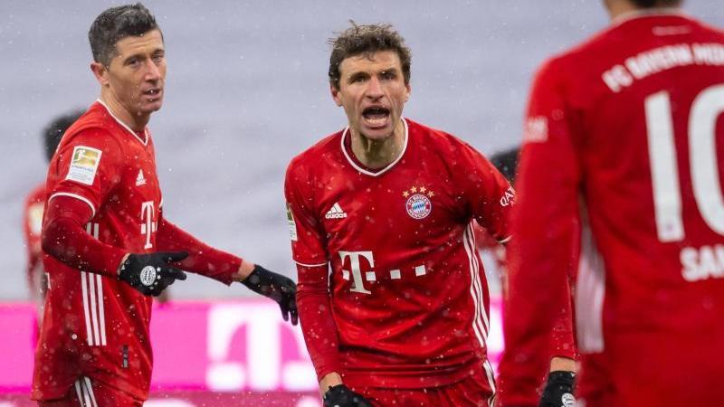 Bayerns Robert Lewandowski (l-r), Thomas Müller und Leroy Sane jubeln über das Tor zur 2:1-Führung gegen den SCFreiburg. Foto: Sven Hoppe/dpa